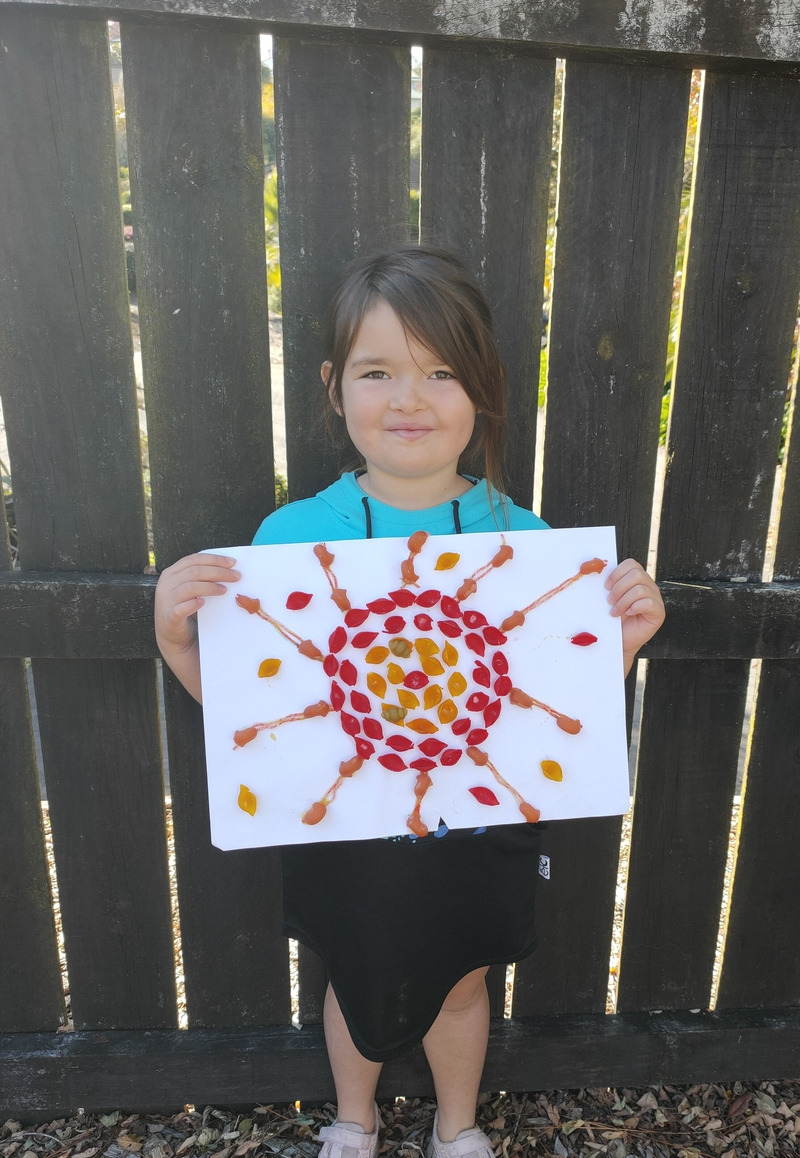 Jade makes the sun from dried and painted pasta