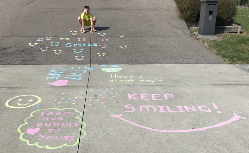 Corbin using the chalk he made to write messages for people