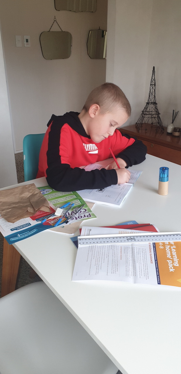 Cory working hard on his Learning at Home pack from the Ministry of Education